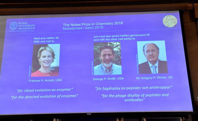 Pictures of the 2018 Nobel Prize laureates for chemistry: Frances H. Arnold of the United States, George P. Smith of the United States and Gregory P. Winter of Britain are displayed on a screen during the announcement at the Royal Swedish