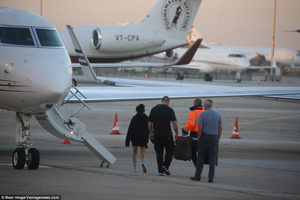assistente e guarda-costas de Kim são retratados com a bagagem como eles embarcar no avião esperando após o ataque terrível