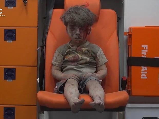 Menino foi resgatado com vida sob os escombros de edifício após bombardeio em Aleppo (Foto: Aleppo Media Center/AP)