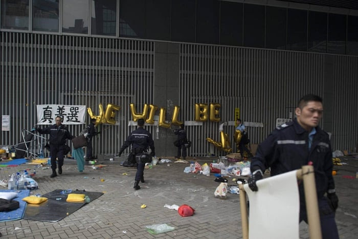 Hong Kong police clear debris from the main pro-democracy protest camp in the Admiralty district. The police began dismantling the site on 11 December, clearing away tents and barricades after more than two months of rallies