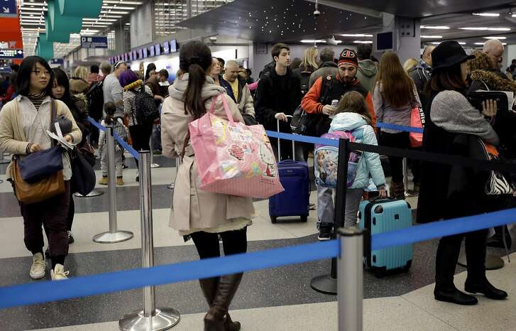 Travelers line up at a security checkpoint area Saturday, Dec. 26, 2015, in Chicago. Airlines are shifting the timing of thousands of flights, even adding dozens of red eyes, as they try to avoid delays while hauling millions of passengers from now through the Christmas weekend. Success or failure could all depend on the weather. (AP Photo/Nam Y. Huh)