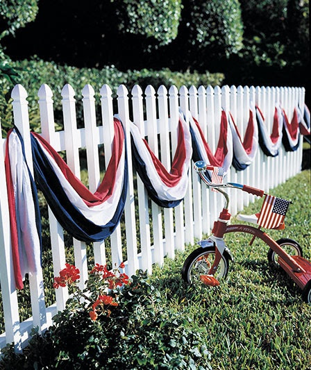 Patriotic Bunting On A White Picket Fence And Red Tricycle With USA Flag