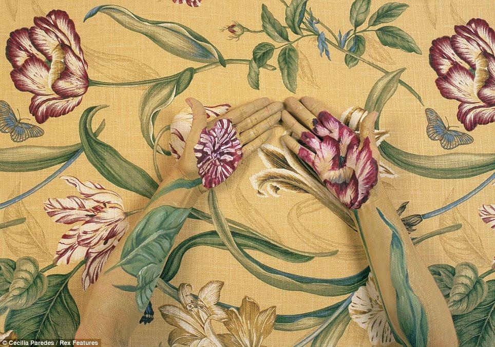 """Trabalhando apenas como camuflagem, o efeito da pintura torna difícil distinguir as mãos Ms Paredes """"do papel de parede"""