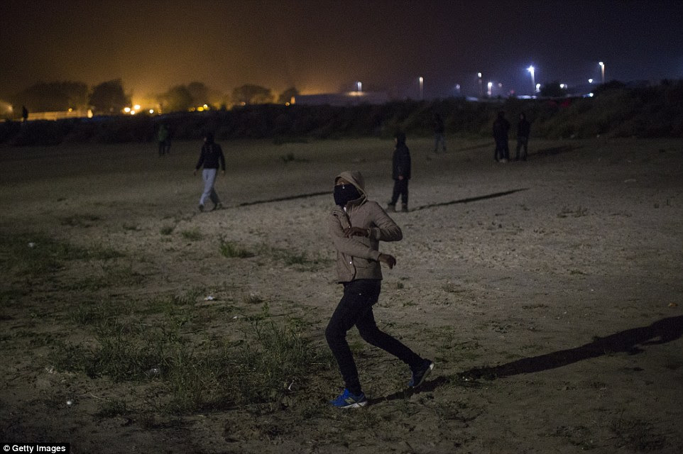 Some of the migrants, many of whom are expected to refuse to leave tomorrow, threw rocks (pictured) at the riot police