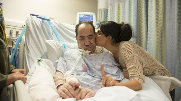In this photo taken in September 2012, Hassan Rasouli is kissed by his daughter Mojgan after he succesfully followed her instruction to lift one finger. After three years in a hospital critical-care bed, at a cost of about $3.5 million, doctors say he has no chance of recovery.