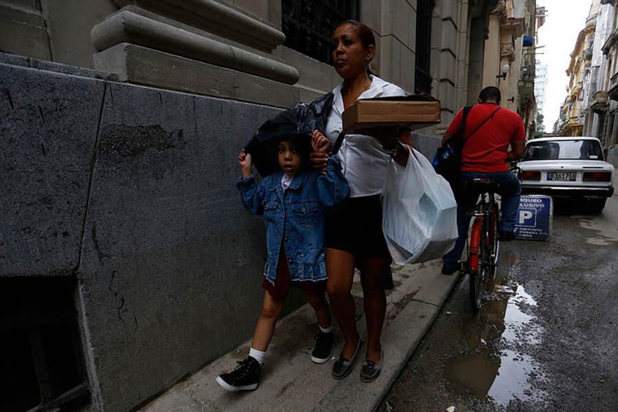 Una madre camina junto a su hija, en la Habana Vieja, en la capital de Cuba, tras recogerla de la escuela. En este país caribeño, las tareas del cuidado están a cargo casi exclusivo de las mujeres.