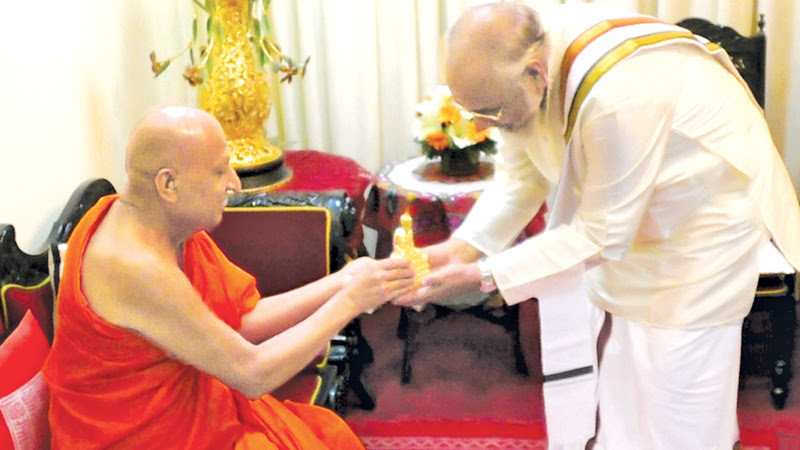 """The Most Ven. Tibbotuwawe Sri Siddhartha Sumangala Mahanayake Thera of the Malwatte Chapter presenting a """"Buddha statue"""" as a memento to Northern Province Chief Minister C.V. Vigneshwaran when the latter called on him at his temple in Kandy and received his blessings recently. Picture by Udeni Rajapaksa"""