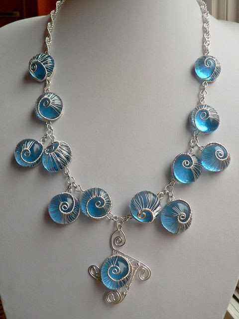 "Blue glass marble and wire woven ""snails"" jewelry. The link has a tutorial you can buy for 10 dollars, and more pics. I like the colors and ethereal effect, but I'm not crazy about the snail motif."