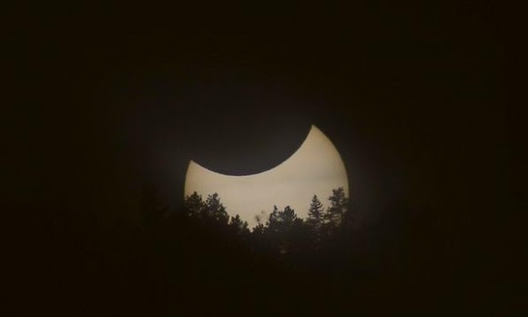 Solar eclipse over the Flatirons near Boulder, Colorado. A syzygy, with the Earth and Moon simultaneously transiting the Sun. Credit and copyright: Alex Parker.