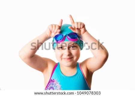 Swimmer: little funny 7 years old cute caucasian girl in cyan swimming costume doing horning gesture. Isolated on white background. Close-up photo