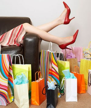Woman lying on couch surrounded by shopping bags
