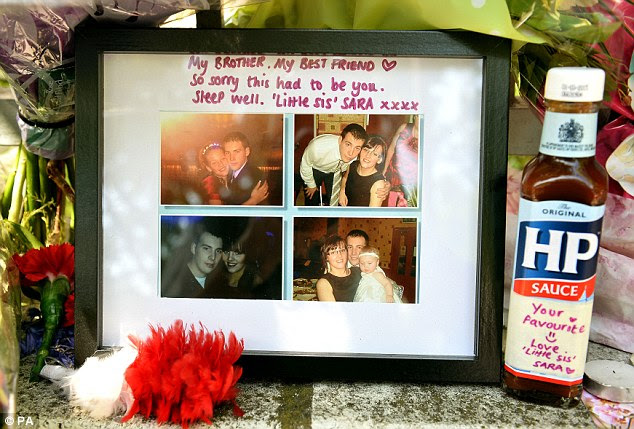 Personal tribute: A framed set of four pictures and a bottle of HP Sauce believed to have been left by Sara, the sister of soldier Drummer Lee Rigby