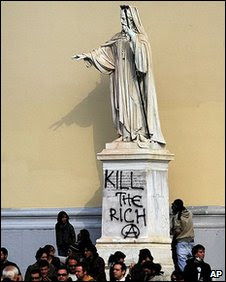 Vandalised statue in Athens - graffiti reads 'Kill the rich'