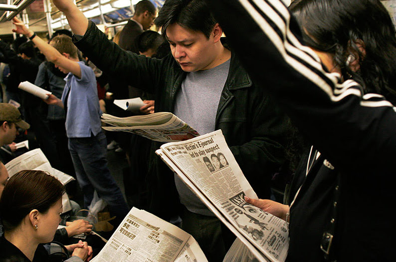 File:NYC subway riders with their  newspapers.jpg