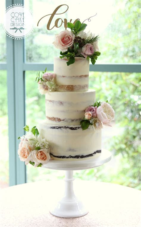 Semi naked wedding cake with fresh flowers and love topper