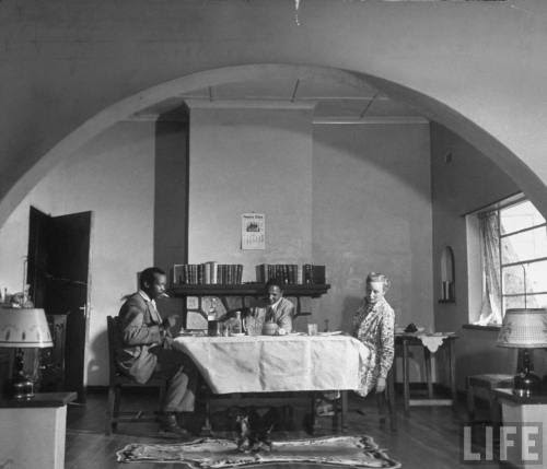 Photograph by Margaret Bourke-White. March 1950, Serowe, Botswana. Source: LIFE Photo Archive, hosted by Google.  Ruth, w. her husband, Bamangwato tribal chief Seretse Khama, eating dinner in sparsely furnished dining alcove w. a visiting native chief as kittens play on antelope skin rug.