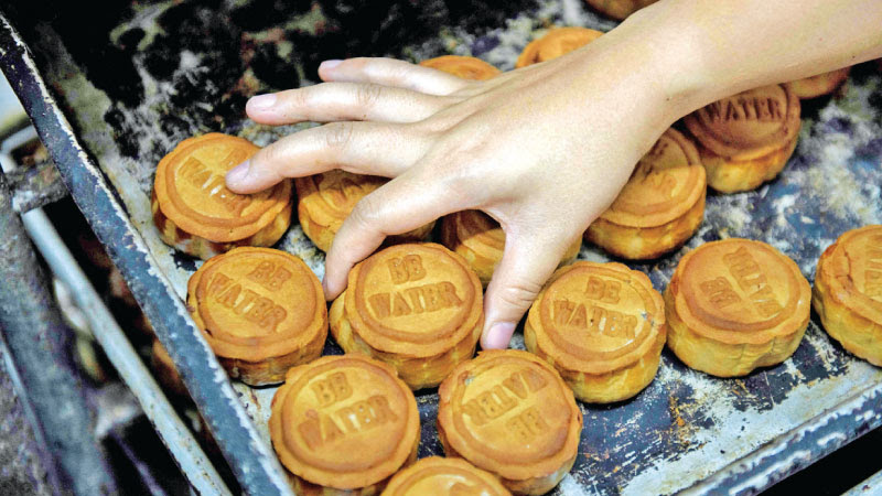 Mooncakes adorned with a popular slogan from recent pro-democracy protests, being prepared for the annual mid-autumn festival at a bakery in Hong Kong. - AFP