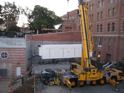 A crane lowers UCLAs pod into its new home, a former loading zone.