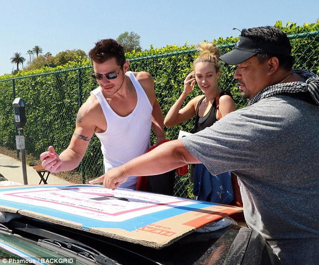 Kind heart: Nick stopped to sign a poster that was reportedly set to benefit hurricane victims