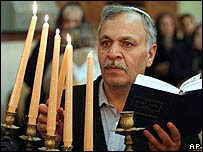 An Iranian Jew lights candles of the Menorah