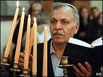 An Iranian Jew lights candles of the Menorah