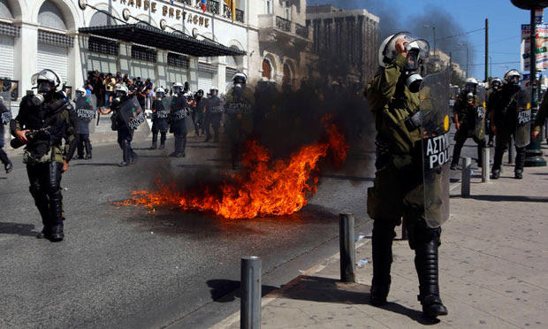 A molotov cocktail explodes beside riot police officers near Syntagma square