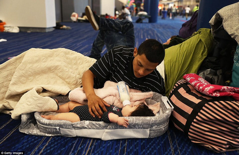 Mark Ocosta feeds his baby Aubrey at the George R. Brown Convention Center on Tuesday
