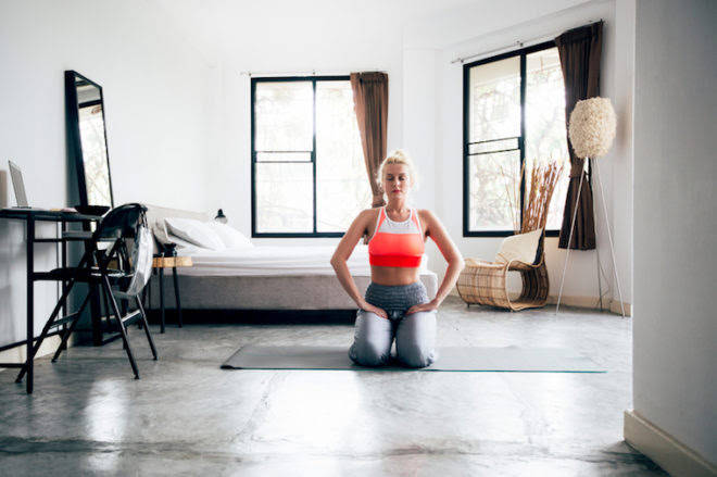 Blonde woman doing yoga indoors.