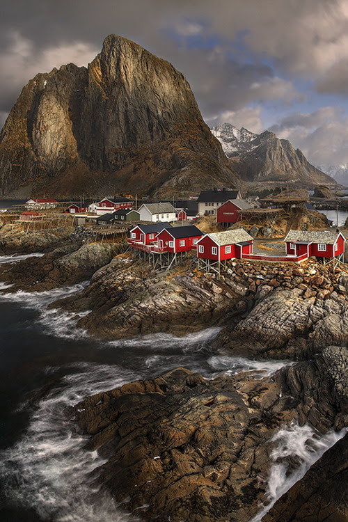 atraversso:  Norway  by Yury Pustovoy  BRIGHT SPOT IN THE DARKNESS Amidst the raging waves of the oceans, thrashing against the jagged rocks, sit pretty red houses on their tall sticks, prepared to weather the worst storms and whatever nature might throw them. Stand strong!