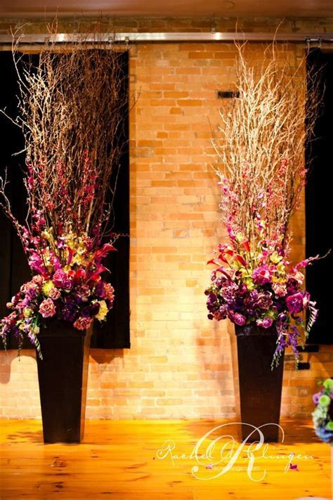 Ceremony urns that combine branches and florals. We like