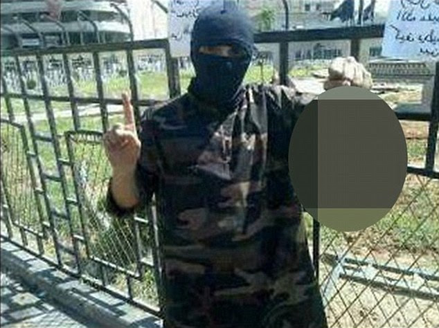 Horrific: This photograph shows British former rapper Abdel-Majed Abdel Bary, 23, holding a decapitated head while standing in Raqqa's central square. Raqqa is ISIS' major stronghold in Syria