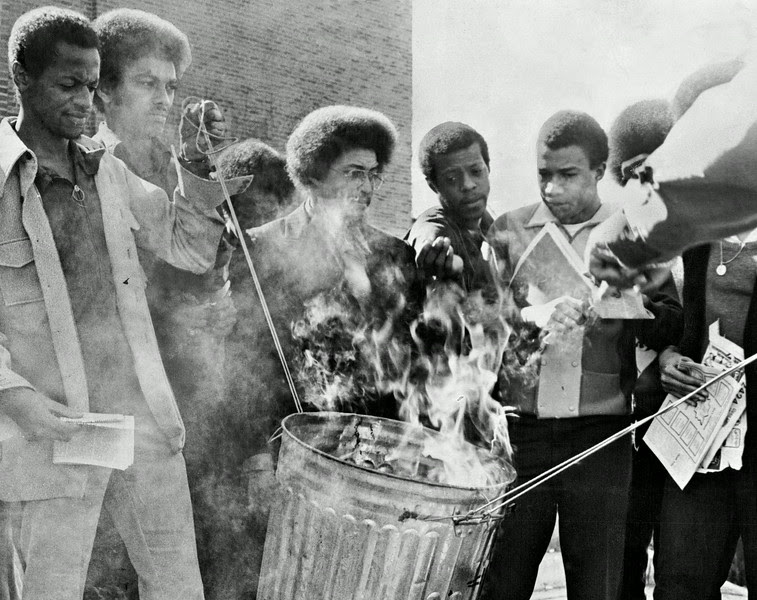 Description of  FEB 23 1972 - A group of University of Denver students protest what they say is lack of news coverage of minority affairs on the campus by the school's newspaper, the Clarion, by burning copies of the paper Wednesday. About 30 students of the Black Student Alliance took part in protest in front of the student union. Russ Richardson, a DU Law school student and Spokesman for the group, said he and other members of the group would try to meet Chancellor Maurice Mitchell to discuss grievances. (Bill Peters/The Denver Post)