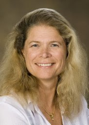 Dr. Ruth Taylor-Piliae poses for a headshot in front of a golden brown backdrop