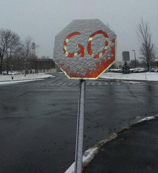 Senyal de STOP coverta de neu, i a sobre amb un dit s'ha dibuixat GO.