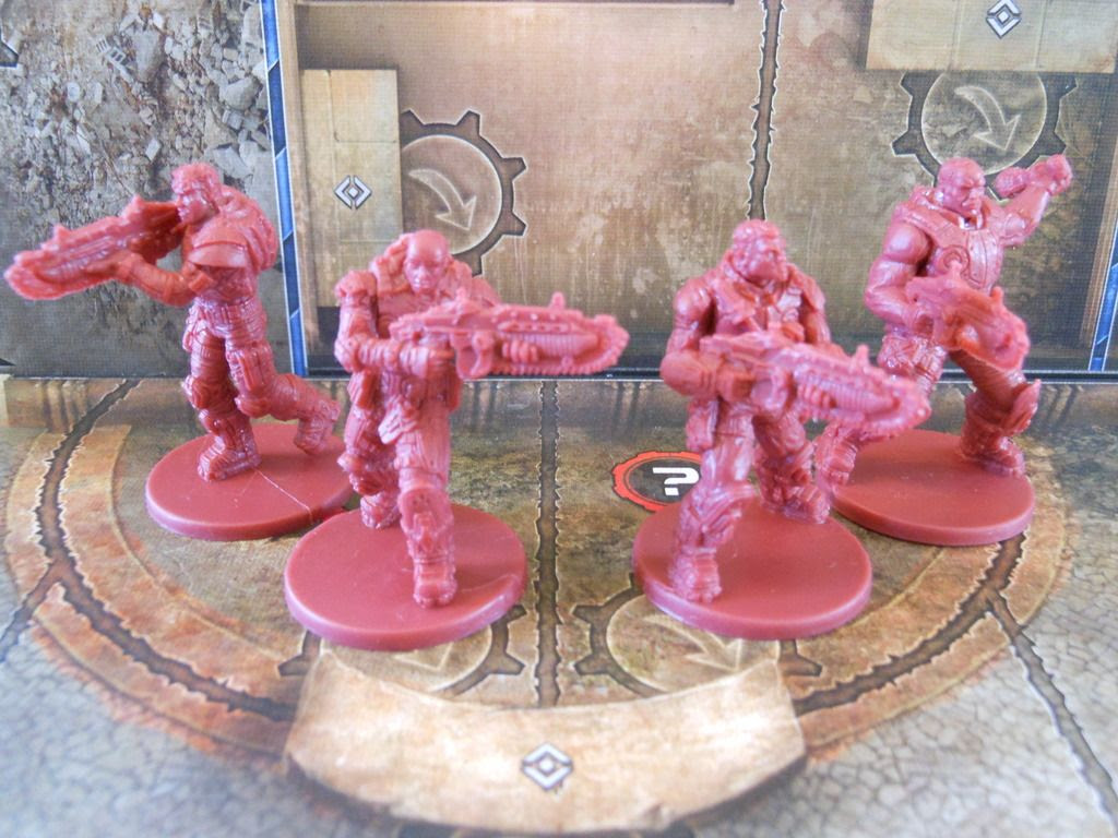 The four hero miniatures from Gears of War, arranged on the game board.