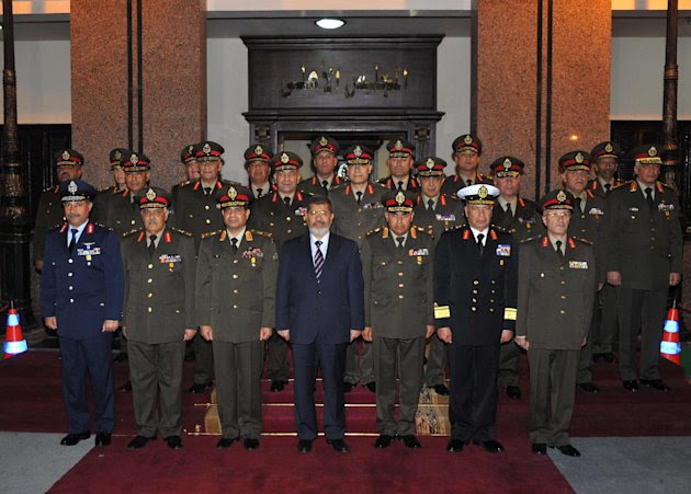 In this Thursday, April 11, 2013 image released by the Egyptian Presidency, Egyptian President Mohammed Morsi, center, poses with military officers after a meeting with the Supreme Council of the Armed Forces in Cairo, Egypt. On Thursday Morsi promoted the heads of Egypt's air force, air defense forces and navy to the rank of Lieutenant-general amid recurrent media reports of strained relations between the presidency and the military. (AP Photo/Egyptian Presidency)