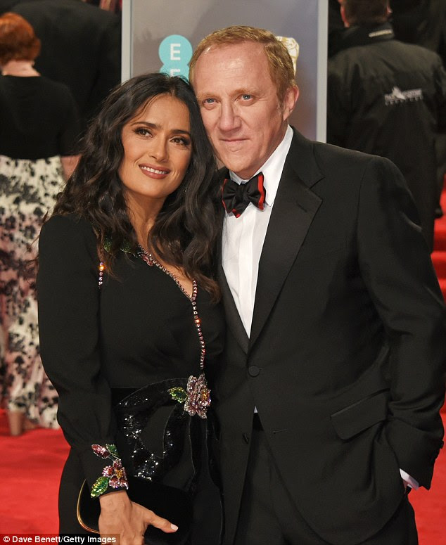 Cuddles: She wore drop earrings and carried a black satin bag as she cosied up to her husband, 55, on the red carpet