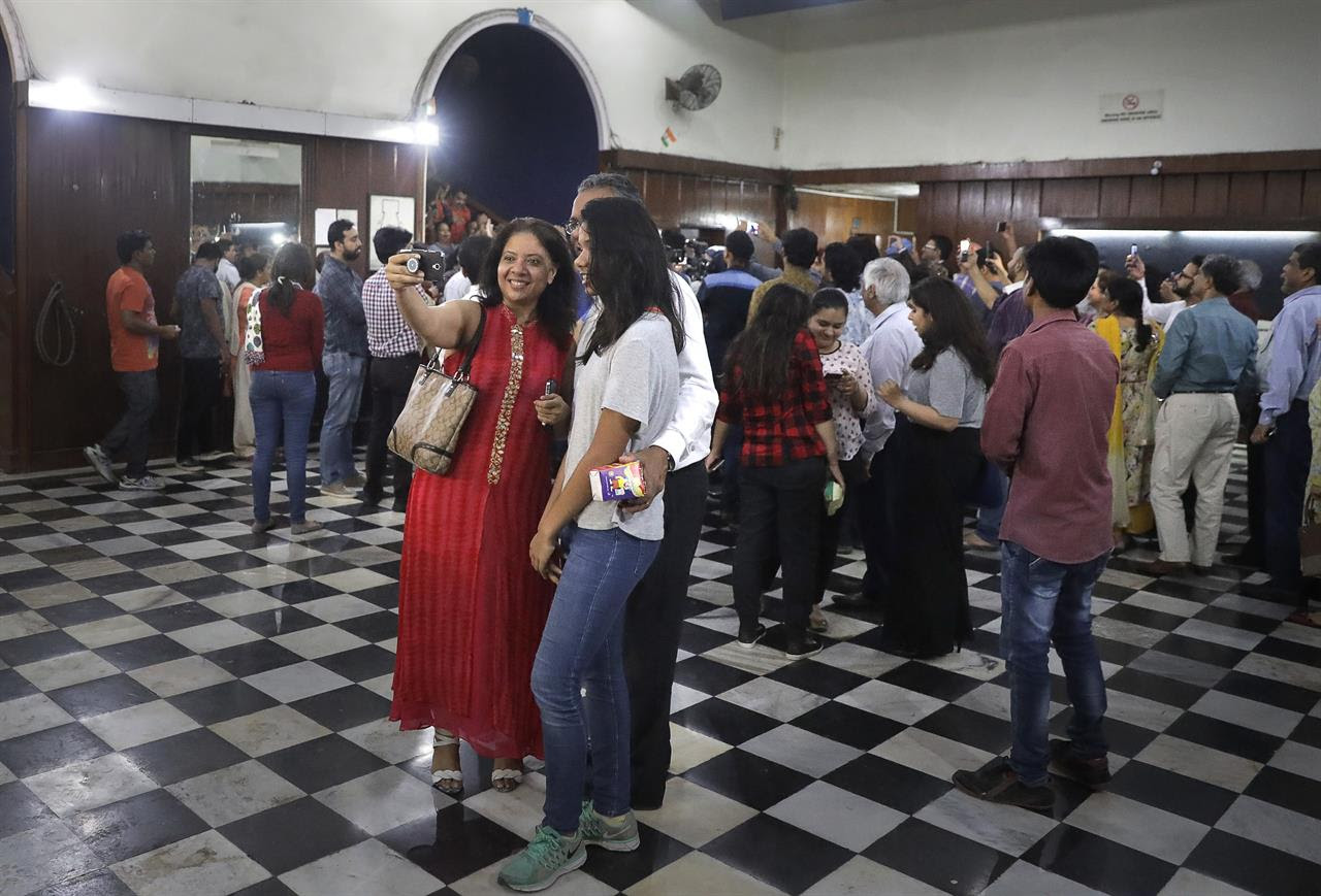 In this early Friday, March 31, 2017 photo, movie buffs sing and take selfies after watching the final movie screening at Regal Theater in New Delhi, India. From Bollywood superstars to political heavyweights, the theater had hosted some of India's biggest names over more than eight decades. But with nostalgic theater-goers singing their way to the exits after a final showing of a Bollywood classic, the iconic New Delhi theater has closed its doors to make way for a multiplex.