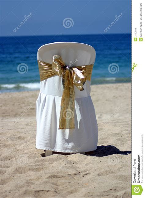 White Chair With Gold Ribbon For A Beach Wedding Stock