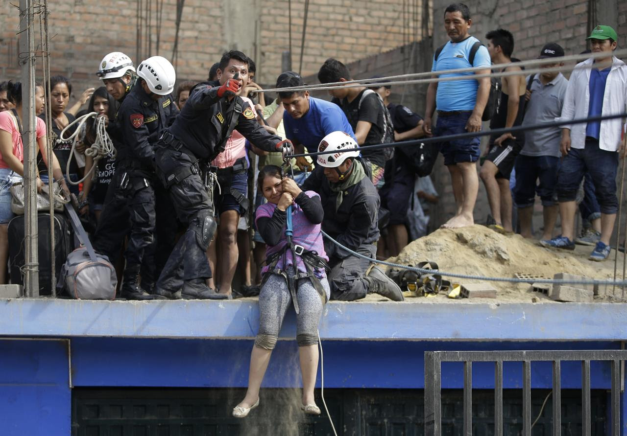A woman is rescued from a rooftop in Lima, Peru, Friday, March 17, 2017. Intense rains and mudslides over the past three days have wrought havoc around the Andean nation and caught residents in Lima, a desert city of 10 million where it almost never rains, by surprise.