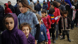 Nens fent cua per recollir menjar i beguda en un campament improvisat a la frontera entre Grècia i Macedònia, a prop d'Idomeni (Reuters)