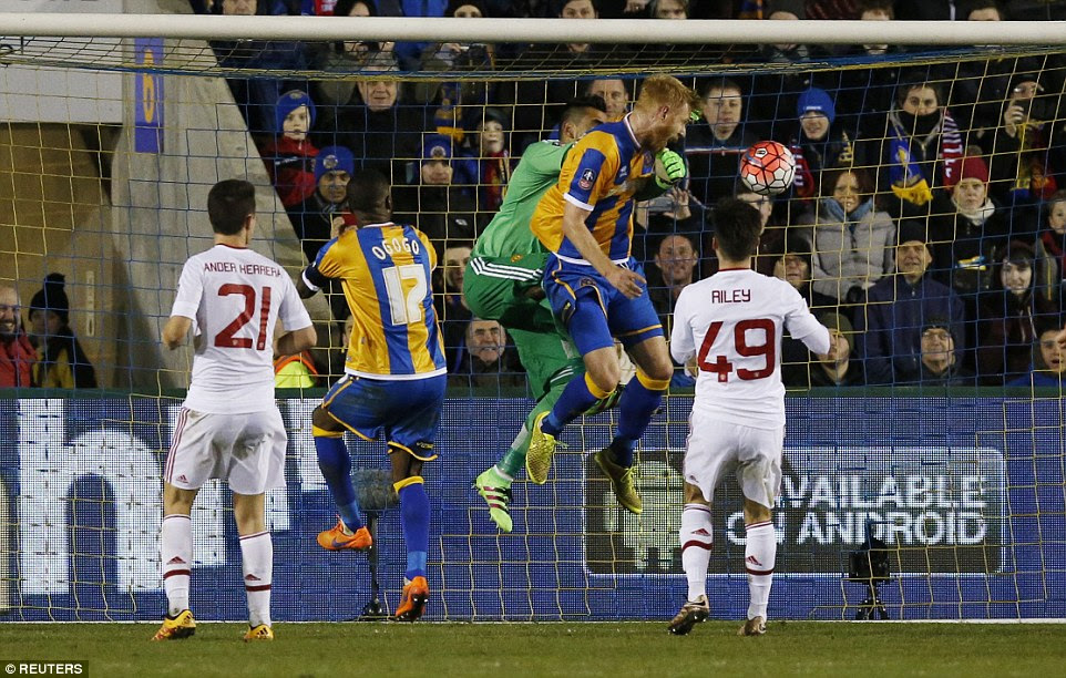 Shrewsbury have a rare foray into the United box and Sergio Romero collides with Zak Whitbread as they go for a cross