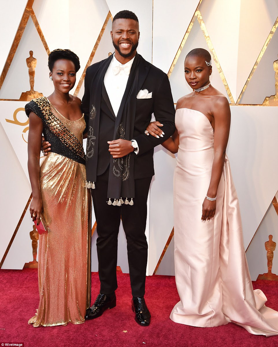 Talented group: The Black Panther beauty's ruched round-neck frock grazed the floor; she carried an on-trend clutch, adding diamond earrings and strappy black heels; pictured with Winston Duke and Danai Gurira