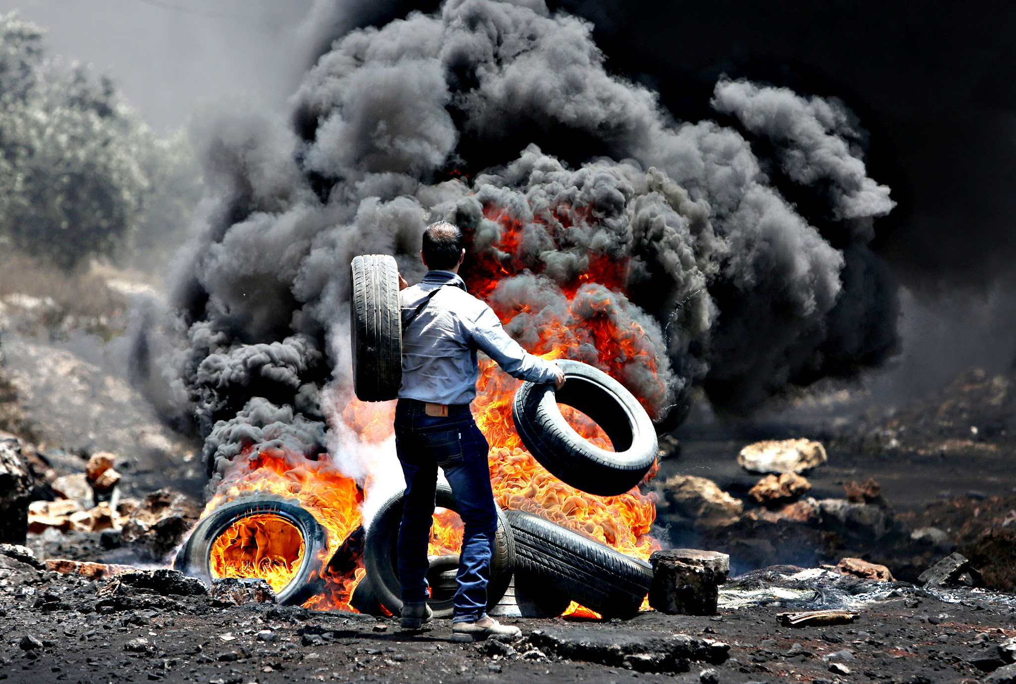 A Palestinian protester throws tires into a fire during clashes with Israeli security forces following a demonstration against the expropriation of Palestinian land by Israel in the village of Kfar Qaddum, near Nablus, in the occupied West Bank, on June 19, 2015.