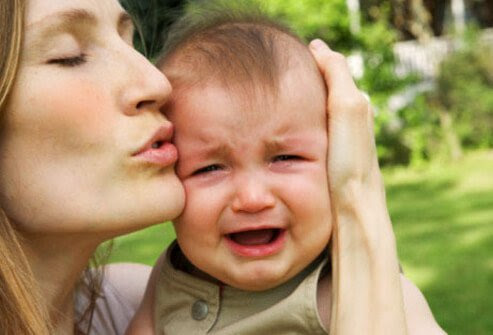 Photo of mother keeping crying baby calm.