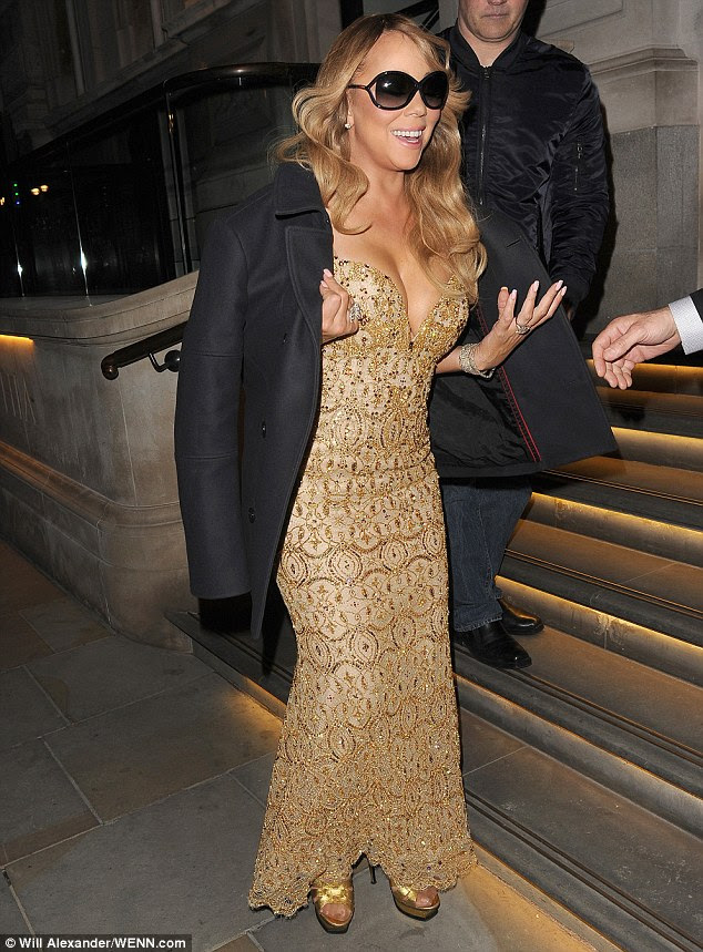 Gold goddess: The Hero hit-maker spilled out of her  figure-hugging, plunging gold gown
