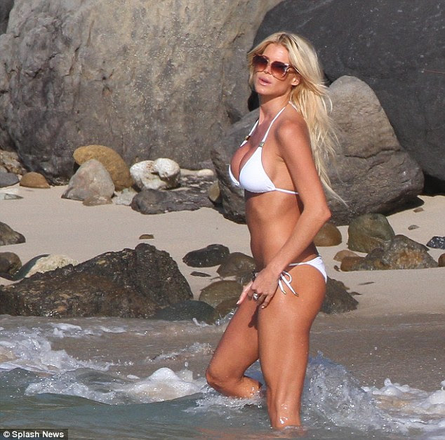 Heating up: Flaunting her ample curves in her favourite white bikini the model looked she was posing for cameras