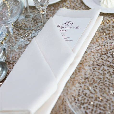 Napkin folding with menu card and a sprig of rosemary