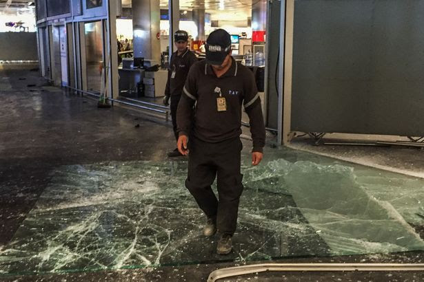 Authorized personnel clear glass debris in Ataturk airport's International arrival terminal