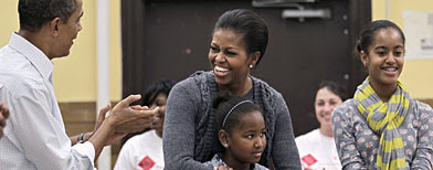 First Lady Michelle Obama embracing her daughter Sasha, 9, is surprised by her husband, President Barack Obama, left. At right is daughter, Malia, 12. (AP Photo/J. Scott Applewhite)